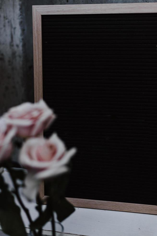 tres rosas rosadas cerca de un tablero negro vacío foto