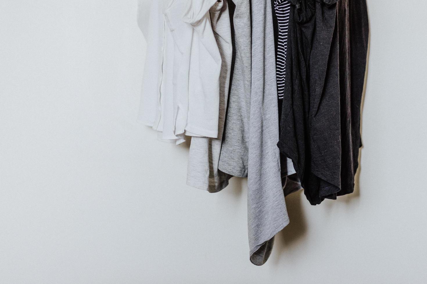 Hanged T-shirts against white background photo