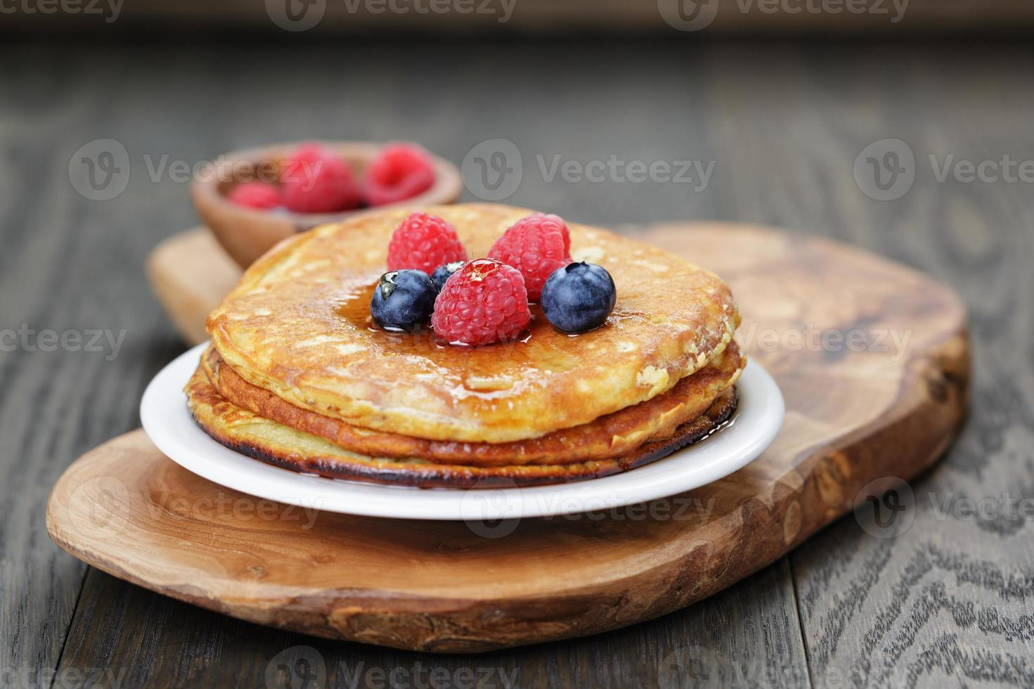 Pancakes with berries and maple syrup, on wooden table photo