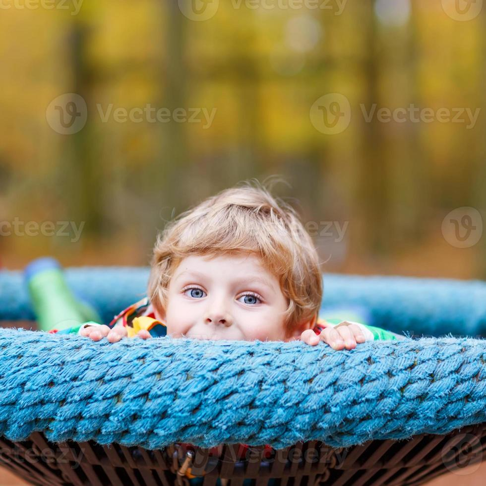 Little kid boy having fun on autumn playground photo