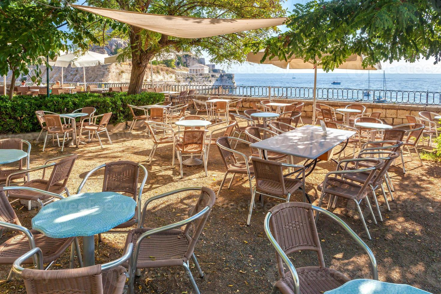 Empty tables in cafe near old venetian fortress photo
