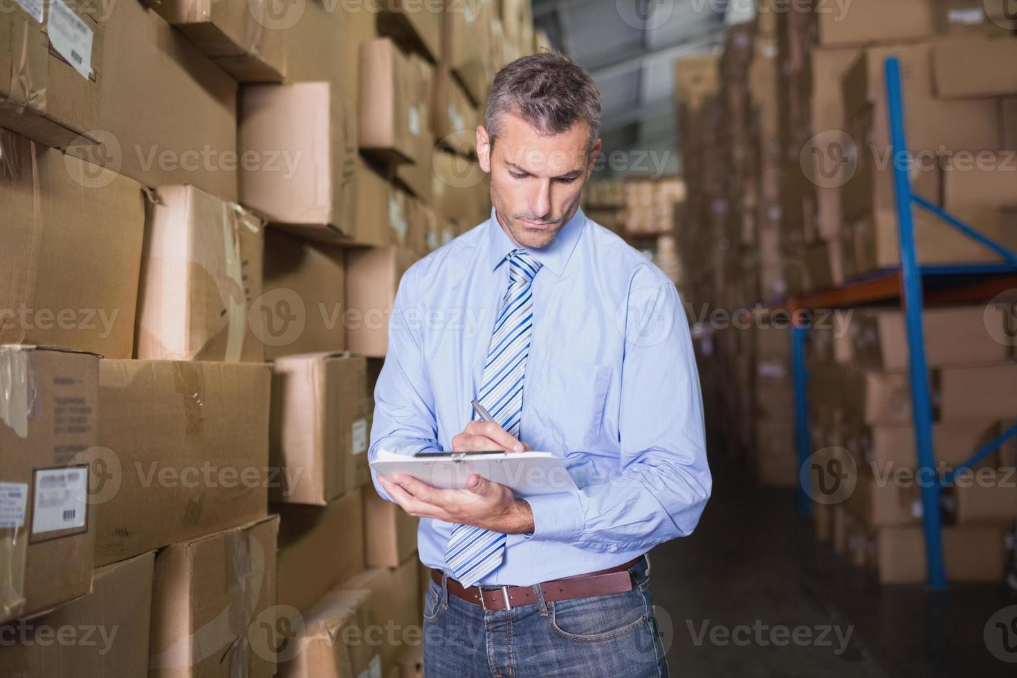 Manager holding clipboard in warehouse photo