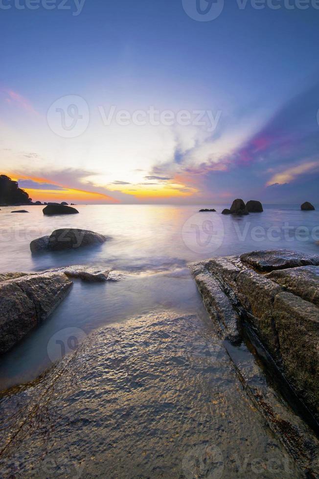 amanecer en la playa tropical rocosa. foto
