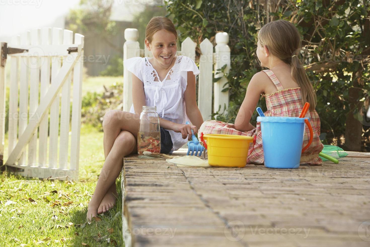 hermanas con juguetes de playa sentado en el patio foto
