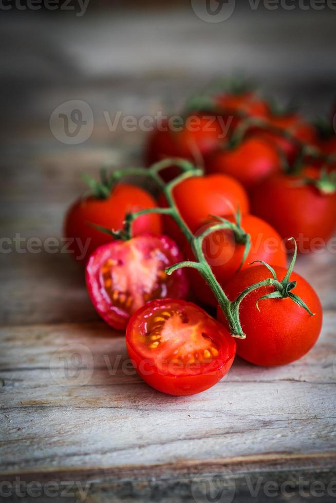 Tomatoes on rustic wooden background photo