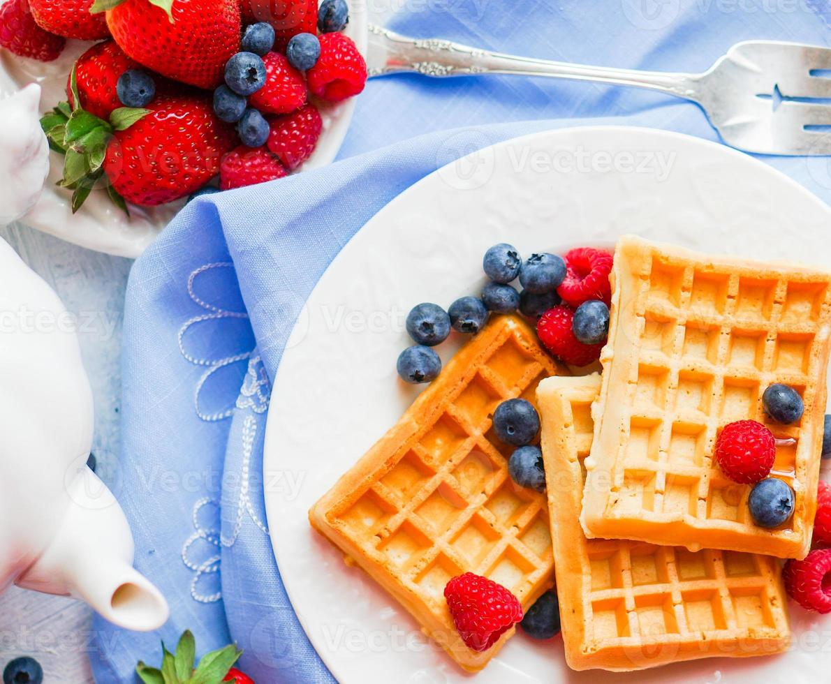 Belgian waffles with berries on rustic background photo