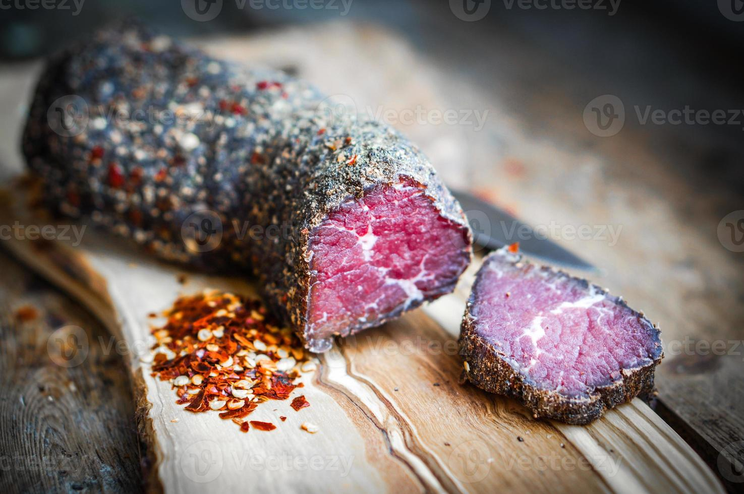 Dried meat with pepper and salt on rustic wooden background photo