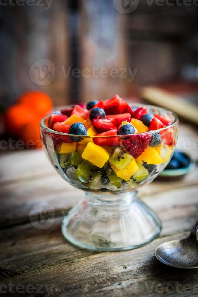 Colorful fruit salad in a jar on rustic wooden background photo