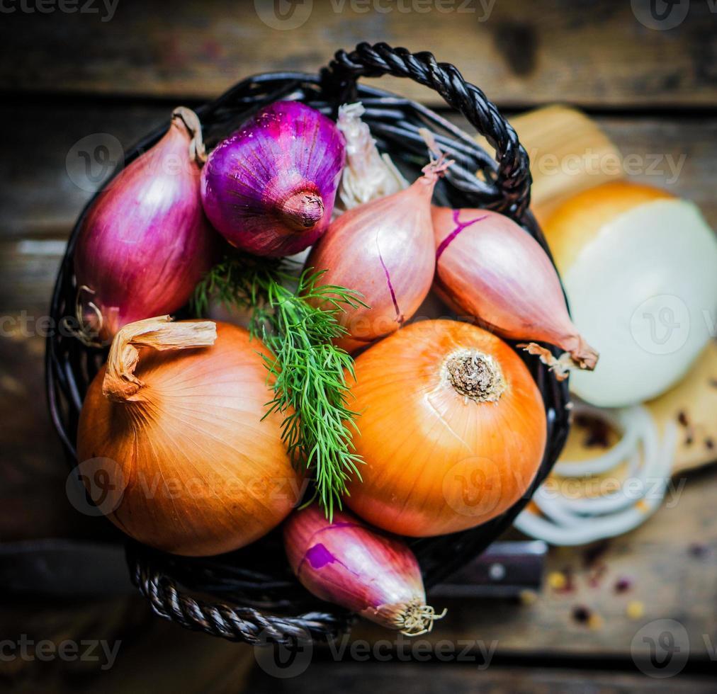 Colorful onions in the basket on rustic wooden background photo