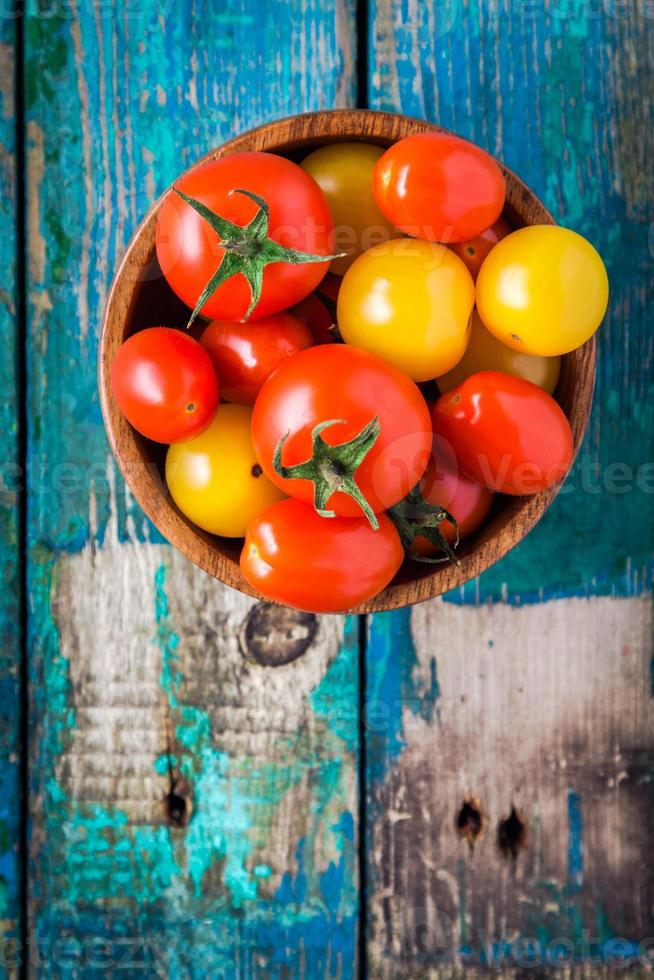 yellow and red cherry tomatoes in bowl on rustic table photo