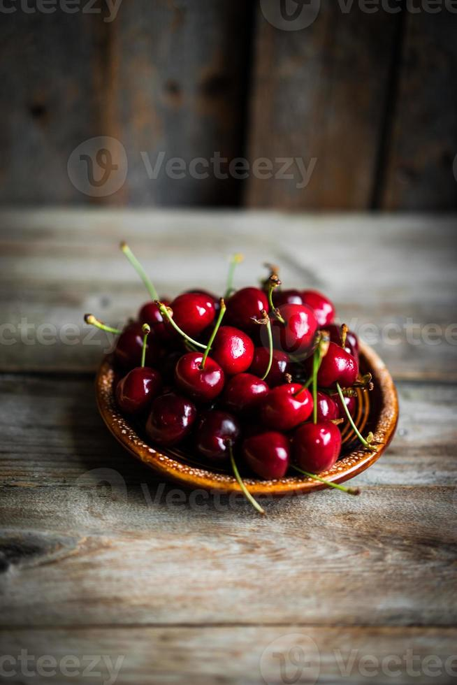 Sweet cherries on rustic wooden background photo
