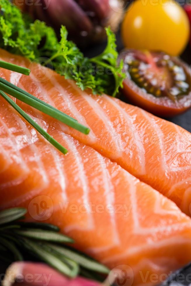 Portion of fresh salmon with spices,herbs and vegetables photo