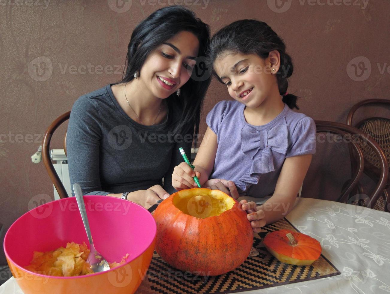 Mother and Daughter Having Fun While Carving a Halloween Pumpkin photo