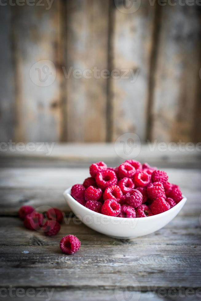 Fresh raspberries on rustic wooden background photo