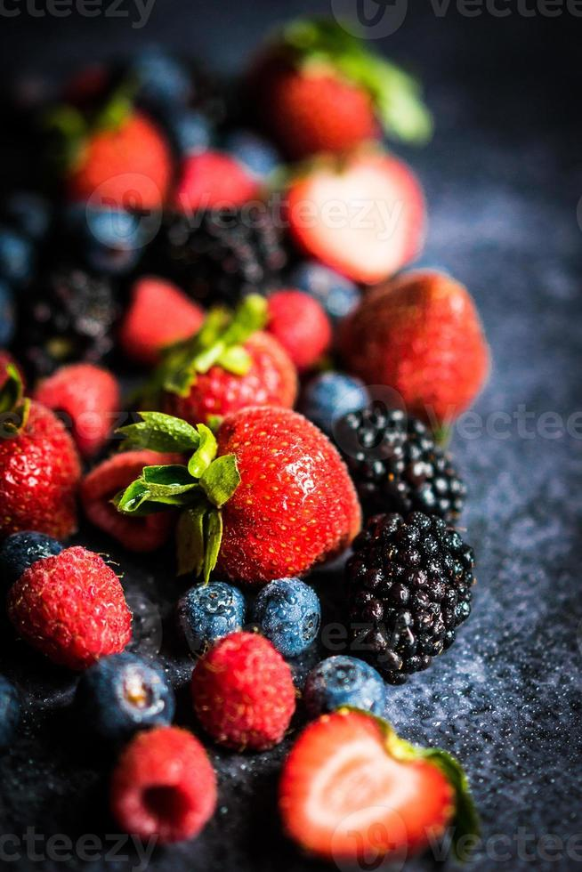 Berry mix on rustic black background photo
