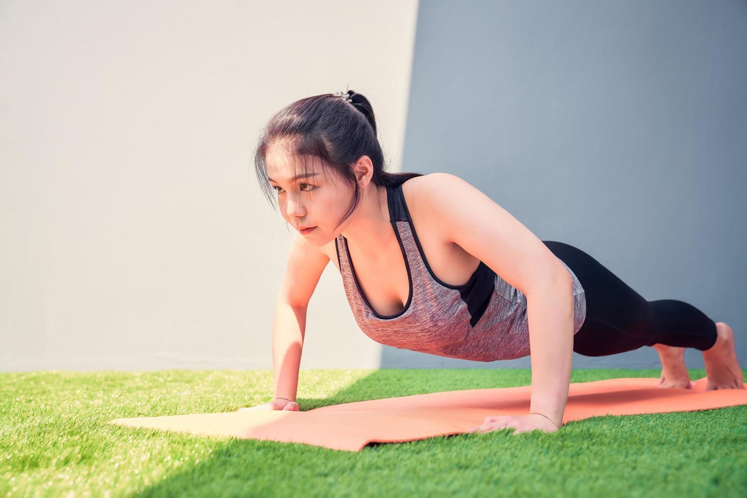 Mujer practicando flexiones en una colchoneta de entrenamiento fuera foto