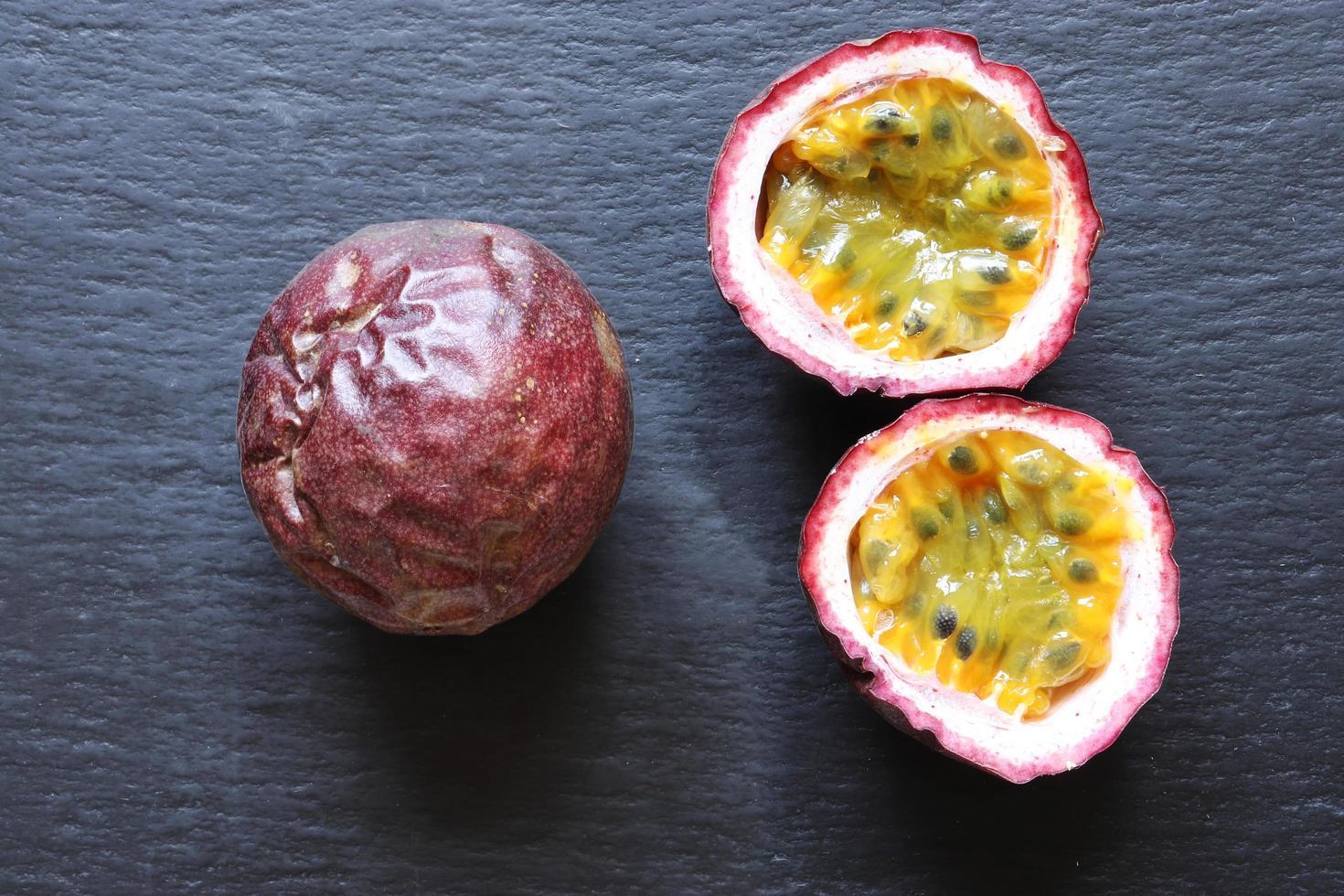 dos frutas de la pasión, una entera, la otra cortada por la mitad foto