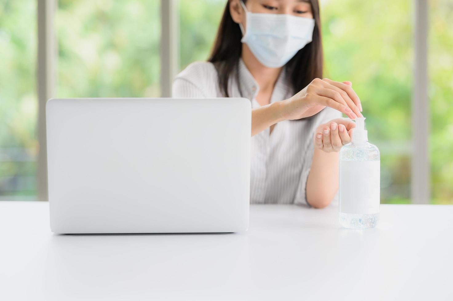 Mujer que llevaba una mascarilla con desinfectante junto a la computadora foto