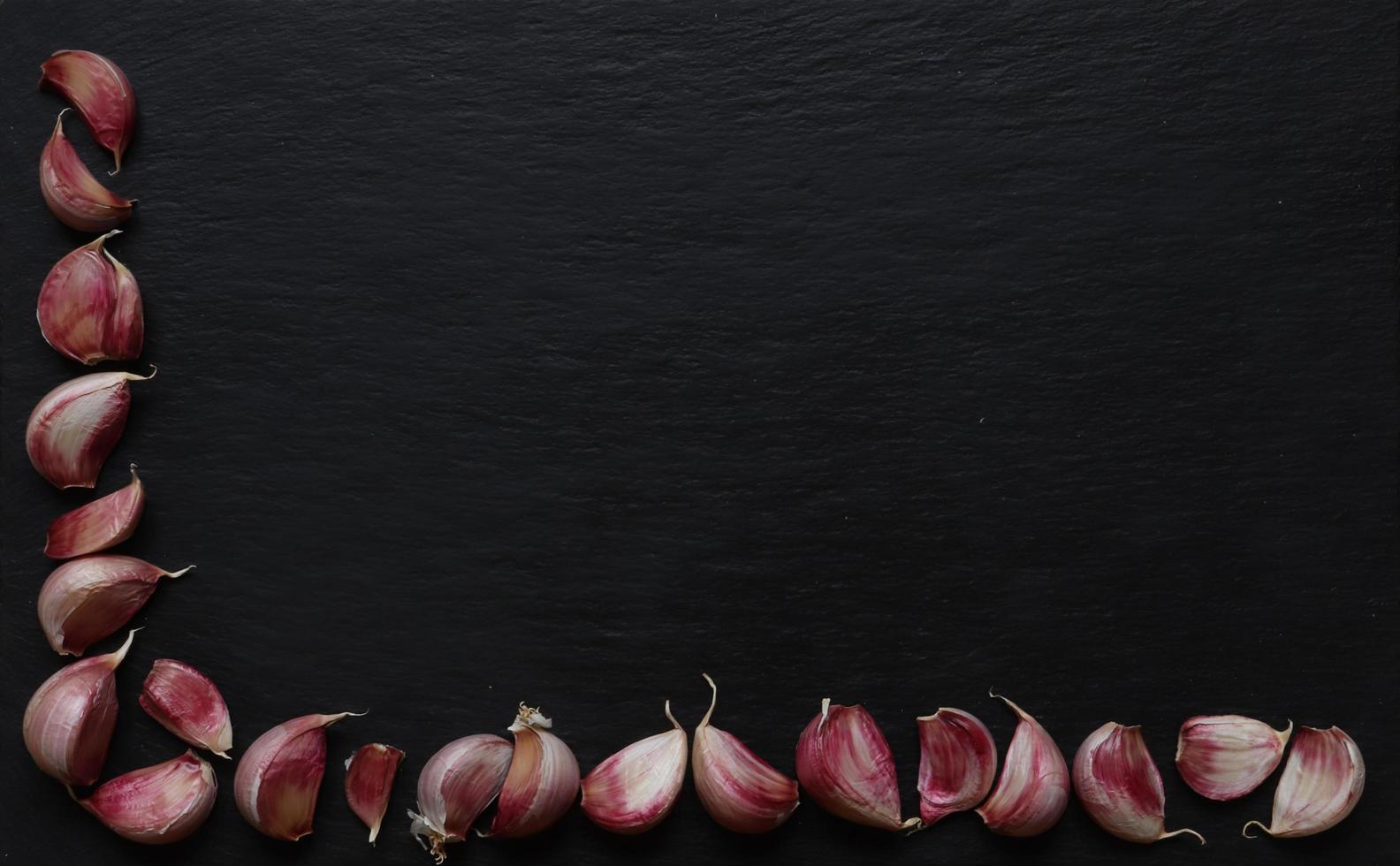 Dientes de ajo sobre fondo de pizarra foto