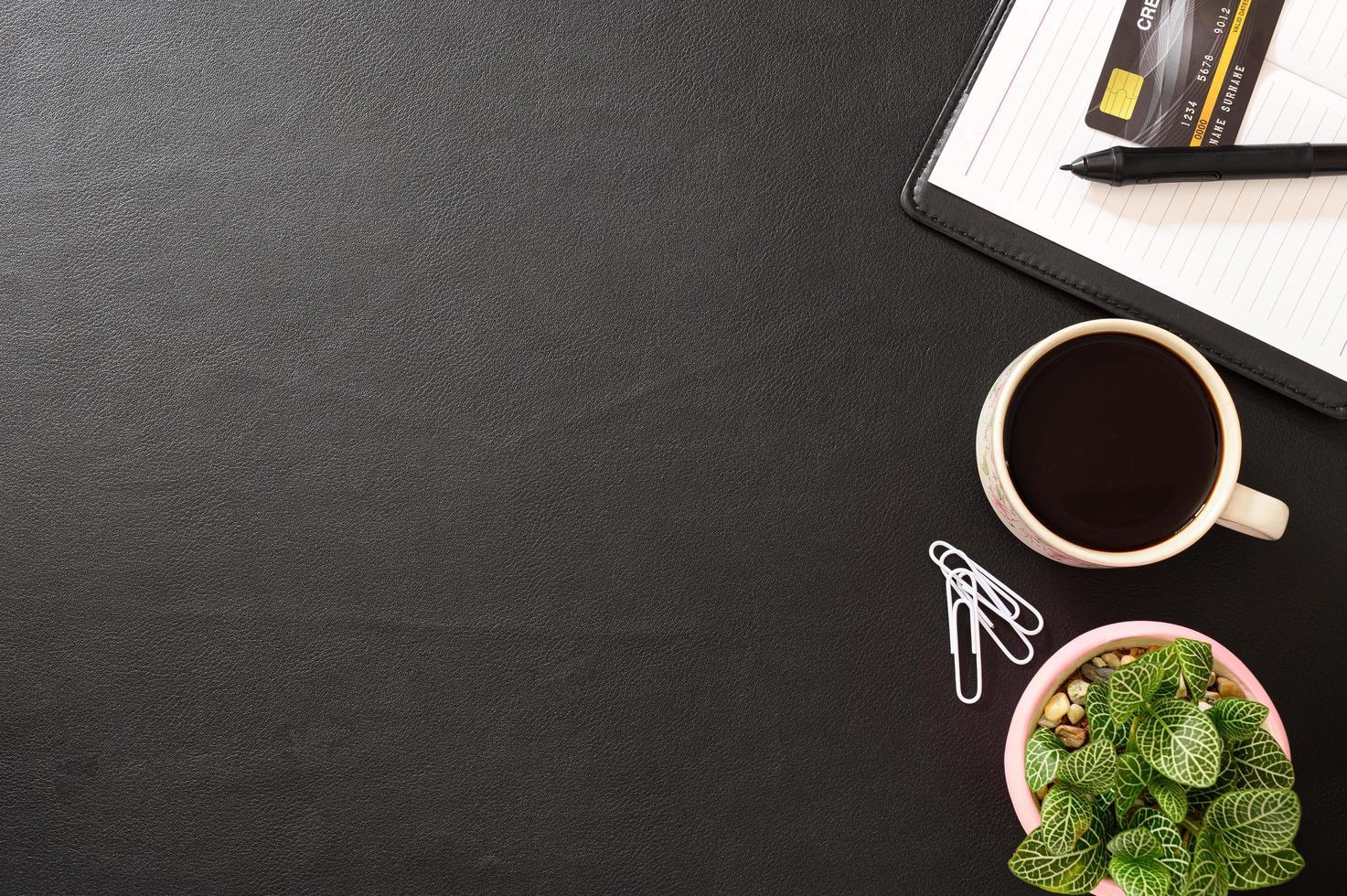 cuaderno, tarjeta de crédito y una taza de café en el escritorio foto