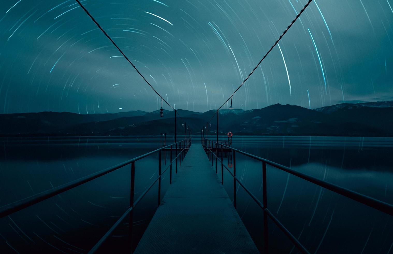 Star trails over seascape bridge at blue hour photo