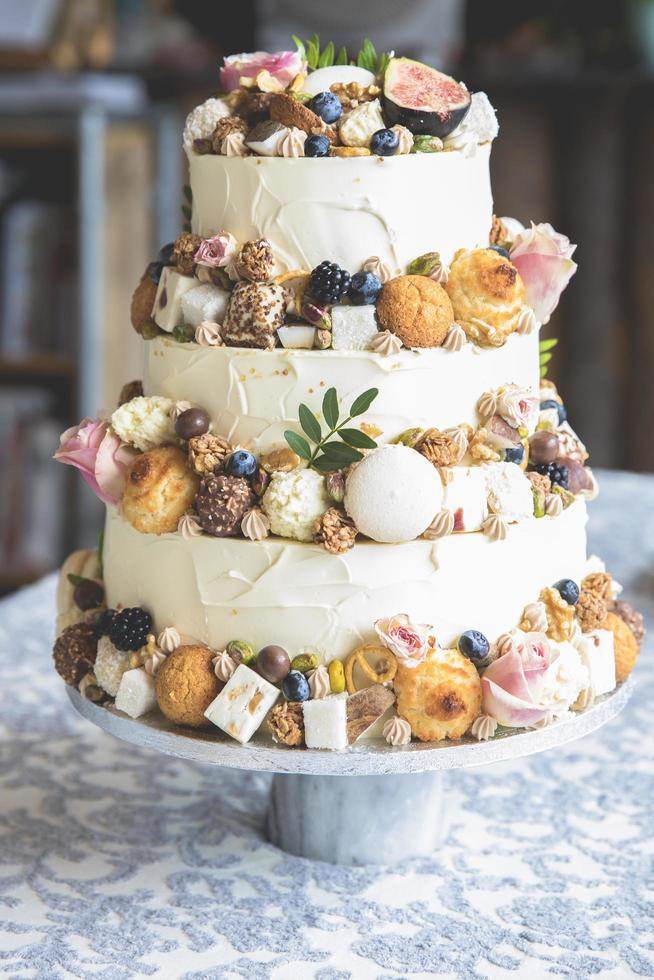 Decorative wedding cake with fruit, biscuits, macaroon and flowers photo
