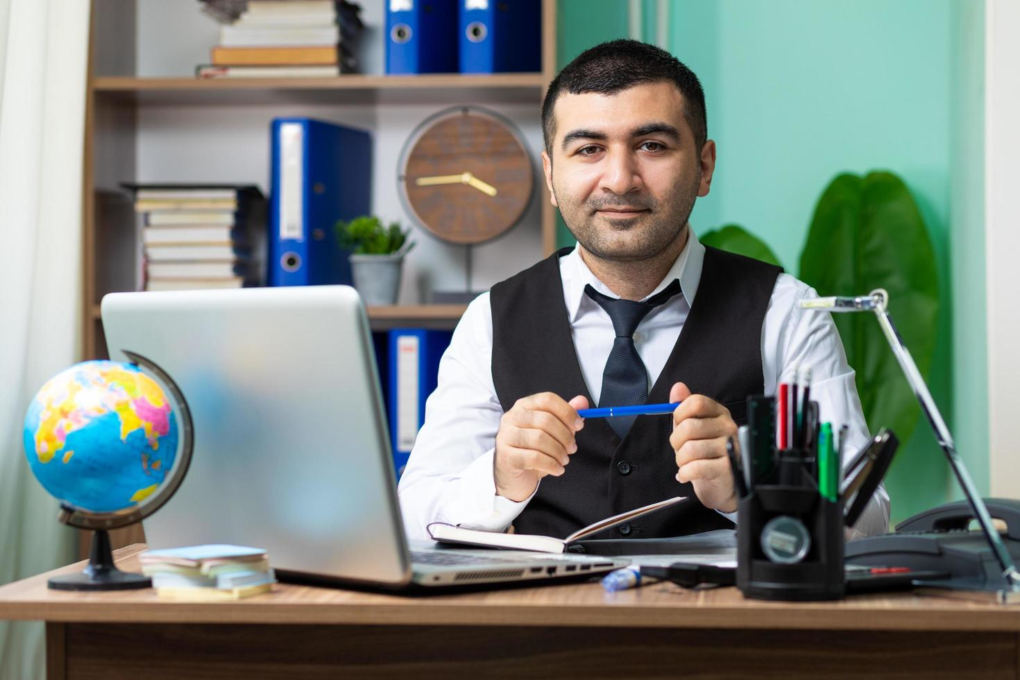 Young business man holding a pen in office photo