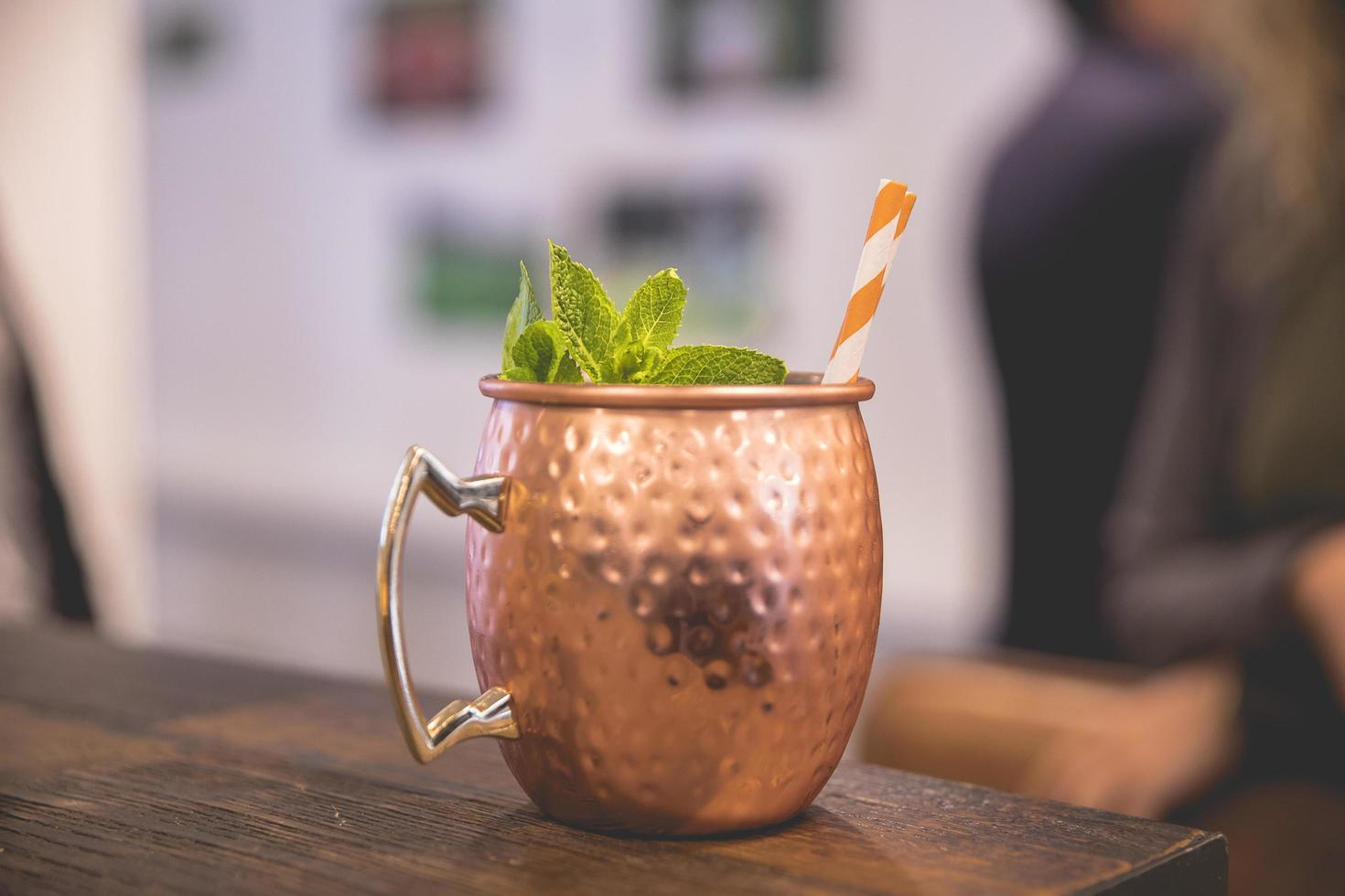 Copper cocktail cup on wooden table photo