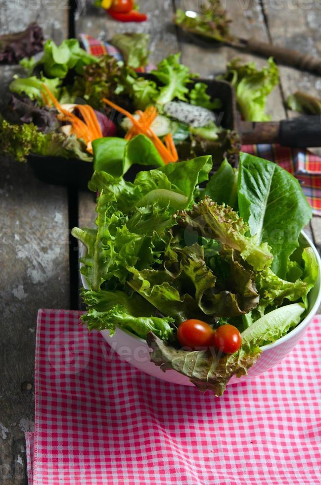 Preparación de ensalada de verduras sobre fondo de tablero de madera foto