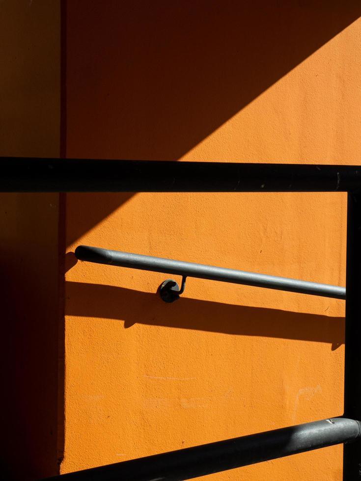 Shadows of rail on orange wall photo