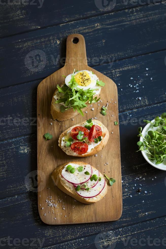 mini toast with radish, egg, arugula and tomatoes photo