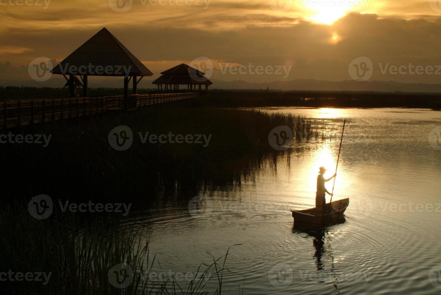 Thai villager punt on lake in Sunset . photo