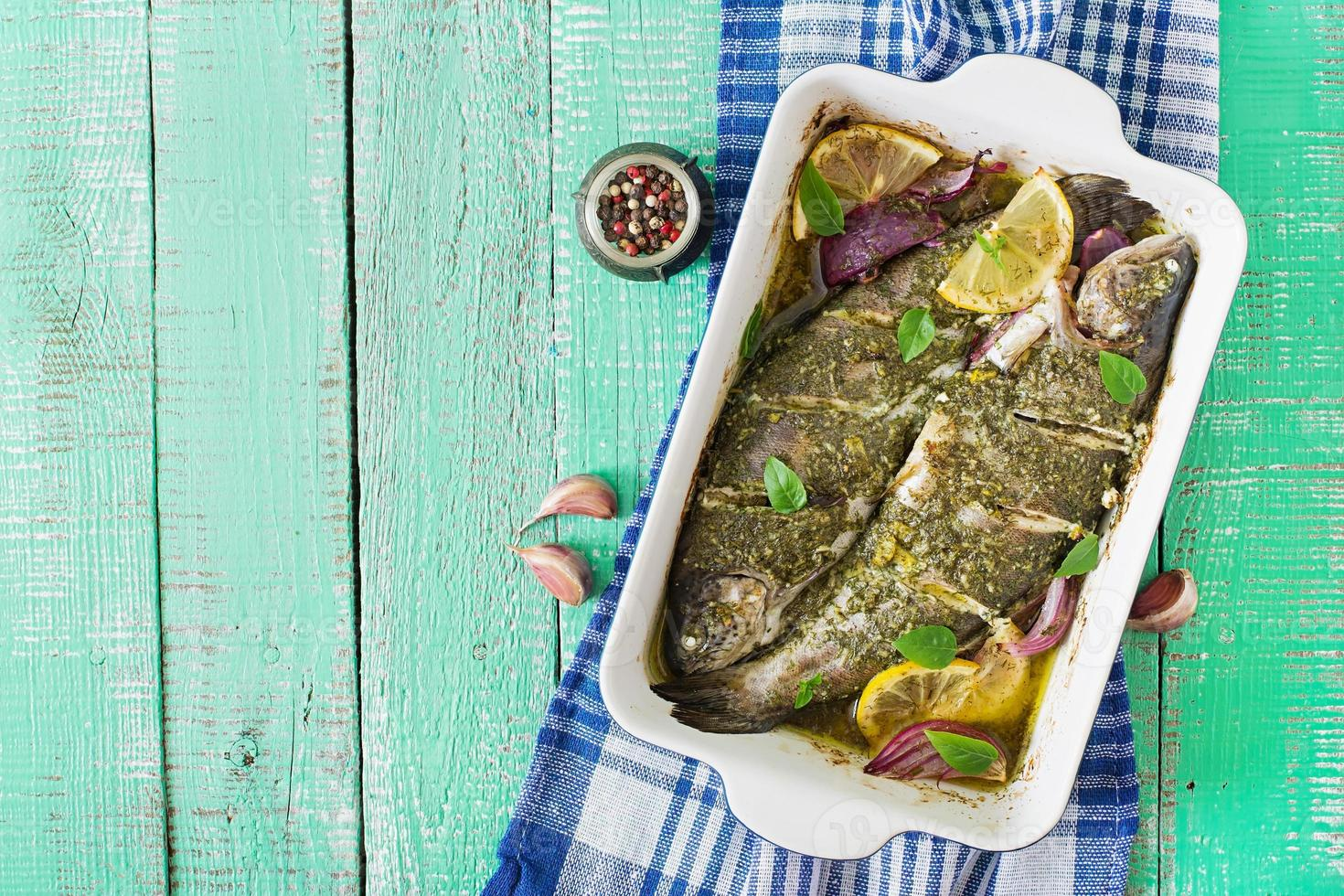 Baked trout  on a bright wooden background. photo