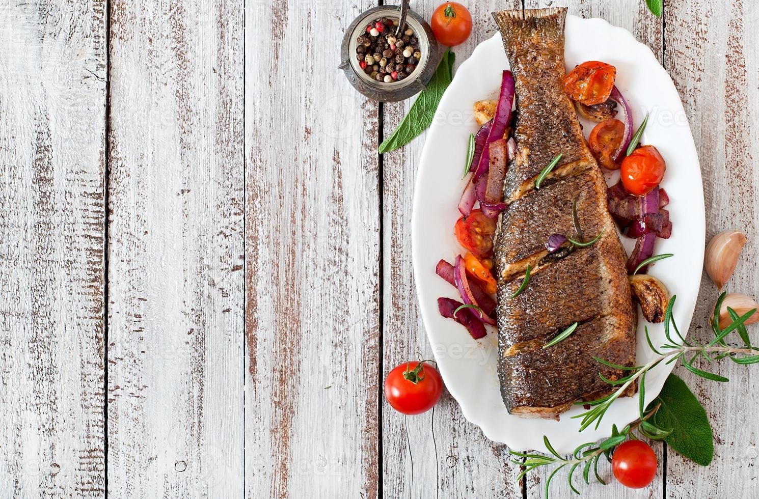 Roasted seabass with vegetables on an old wooden background photo