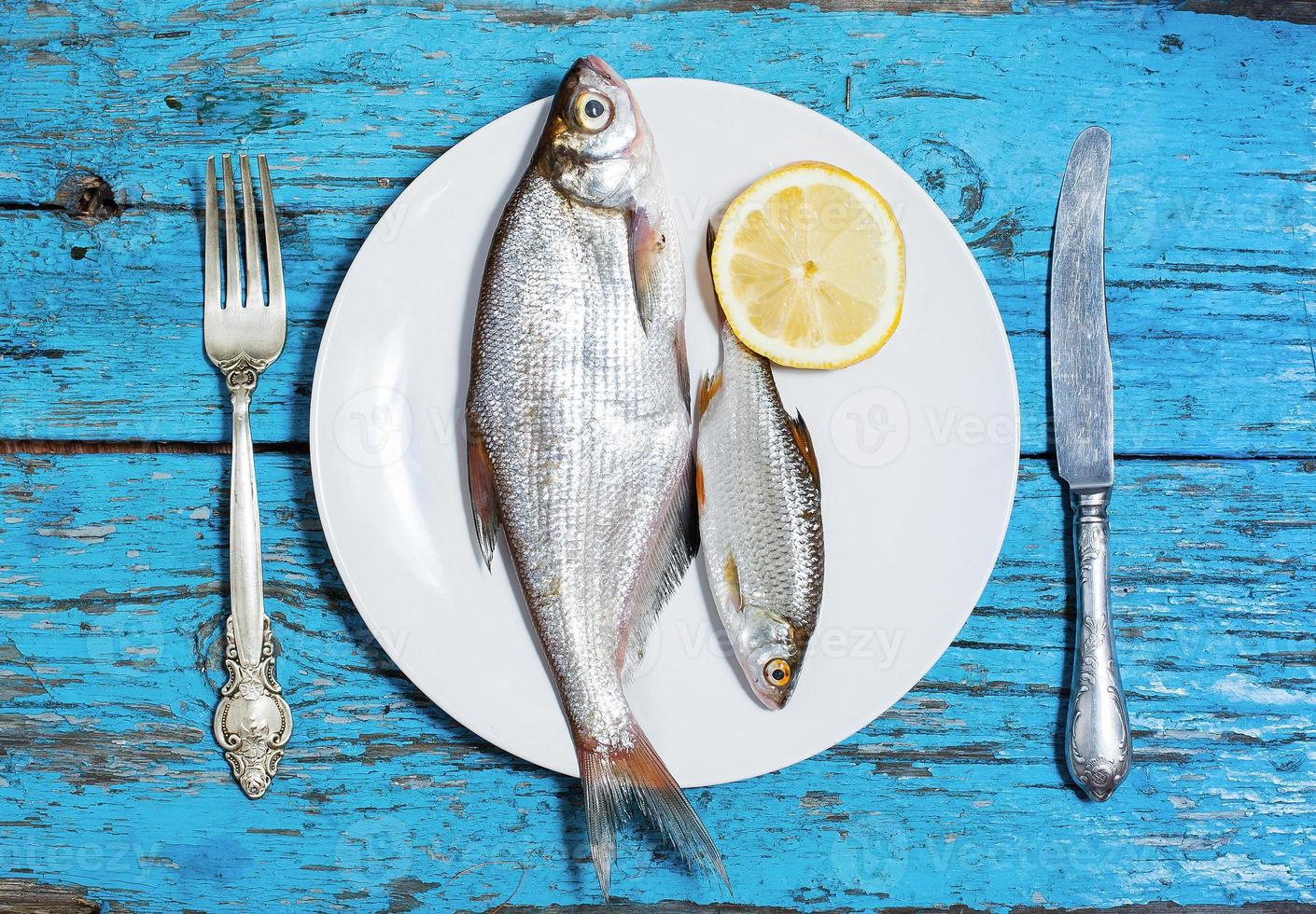 fresh fish on the plate, table setting, wooden background photo