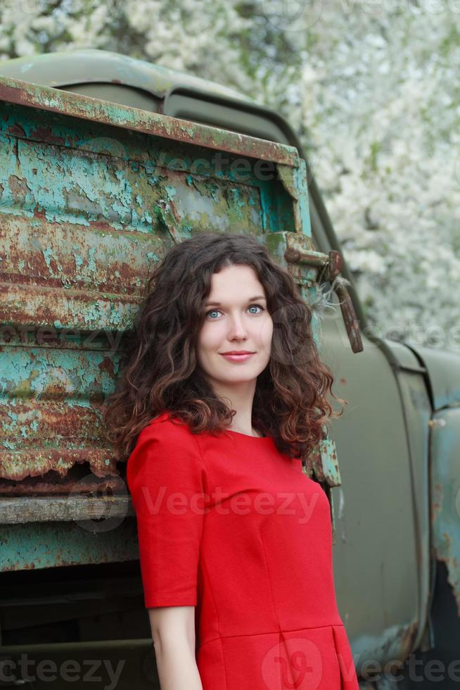 Blue-eyed brunette at old truck body and blooming trees background photo