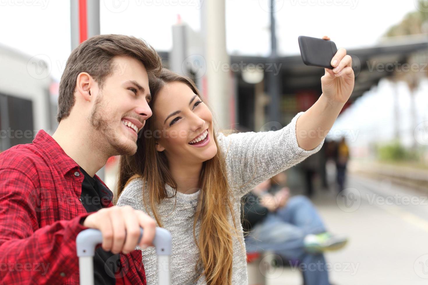 pareja de viajeros fotografiando un selfie con un smartphone foto
