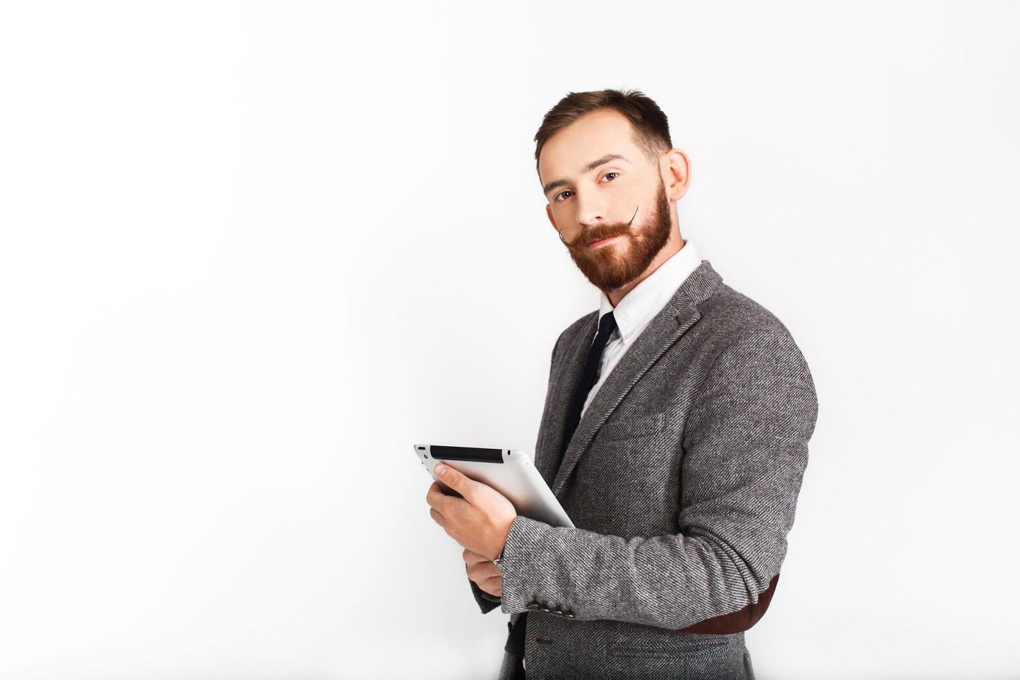 Serious man with red beard poses in gray suit with tablet in his hand photo