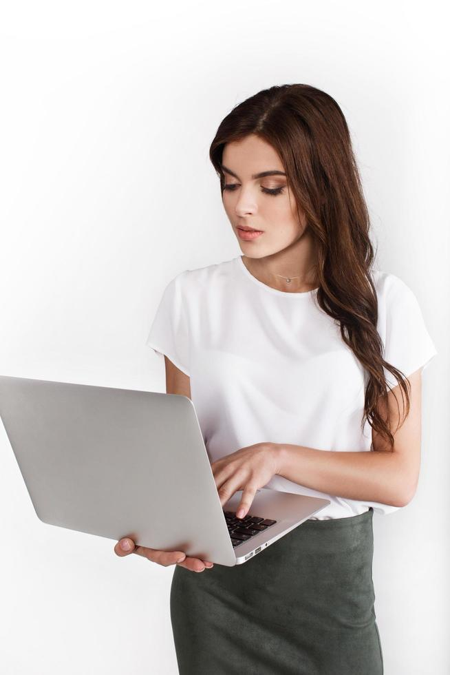 Woman dressed in business style works on laptop on white background photo