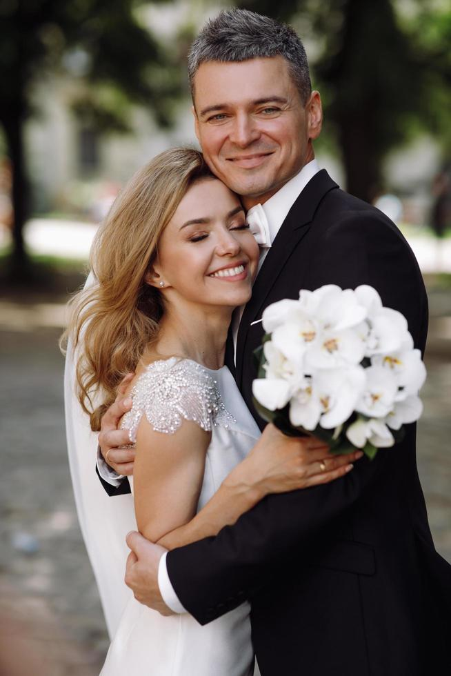Bride and groom embrace in the sunshine photo