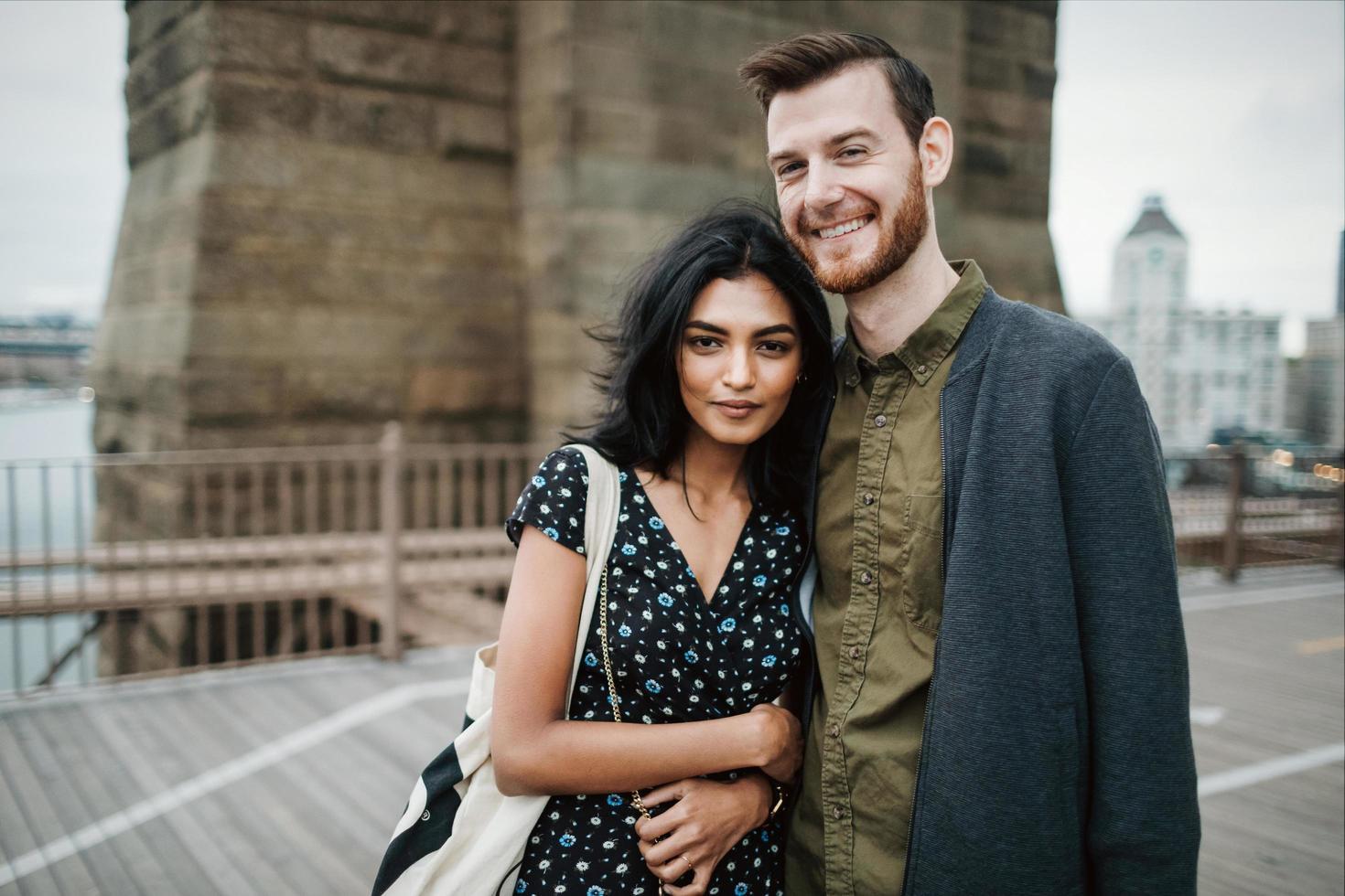 Attractive couple embraces on city bridge photo