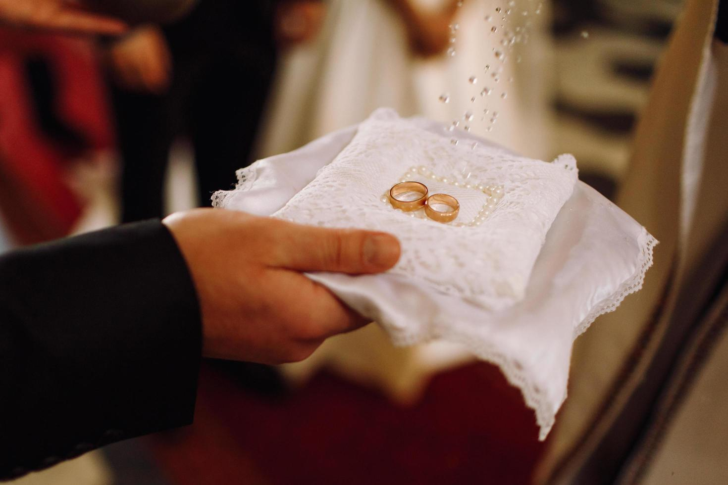 Groom holds golden wedding rings while priest blesses them photo