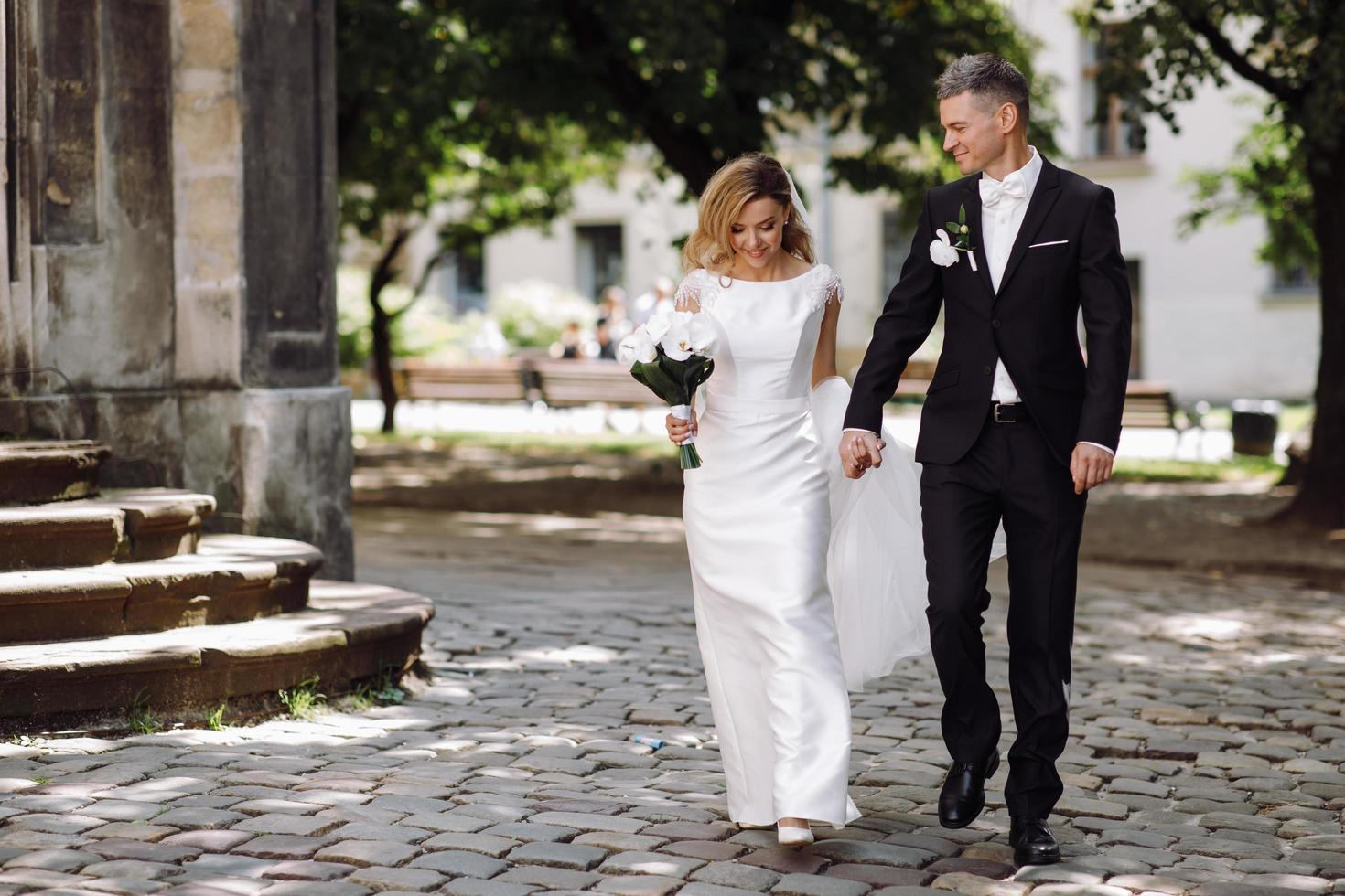 Groom holds bride's hand while walking on cobblestone path photo