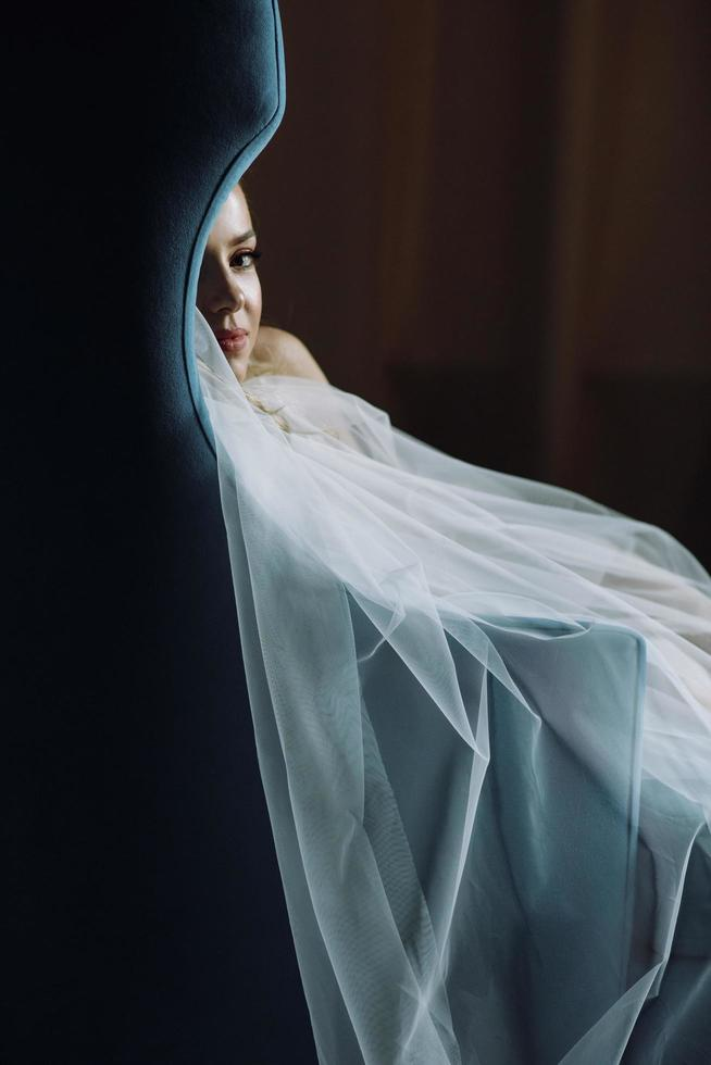 Thoughtful bride sits in a deep blue chair in dark hotel room photo