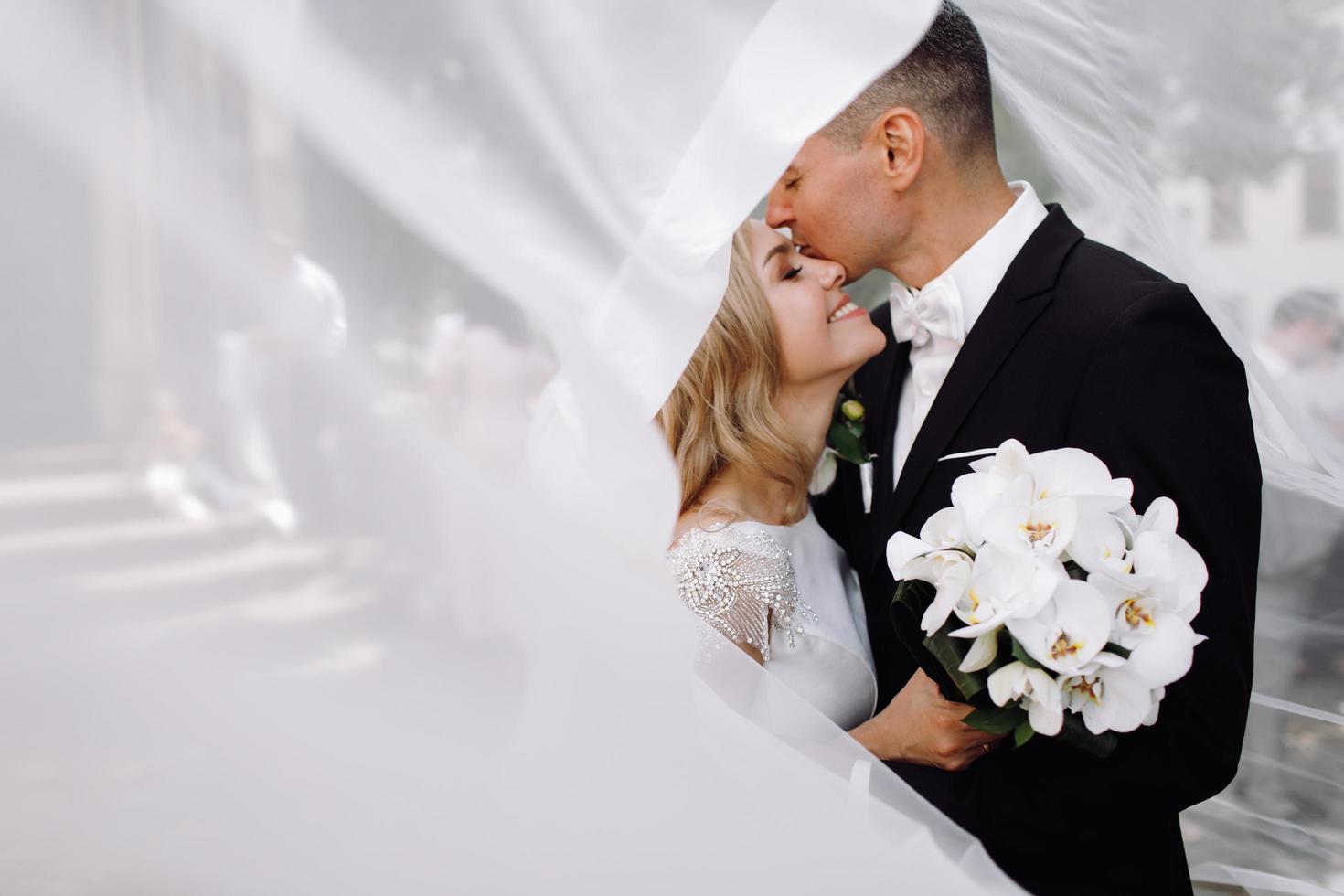 la novia y el novio se abrazan bajo el sol foto