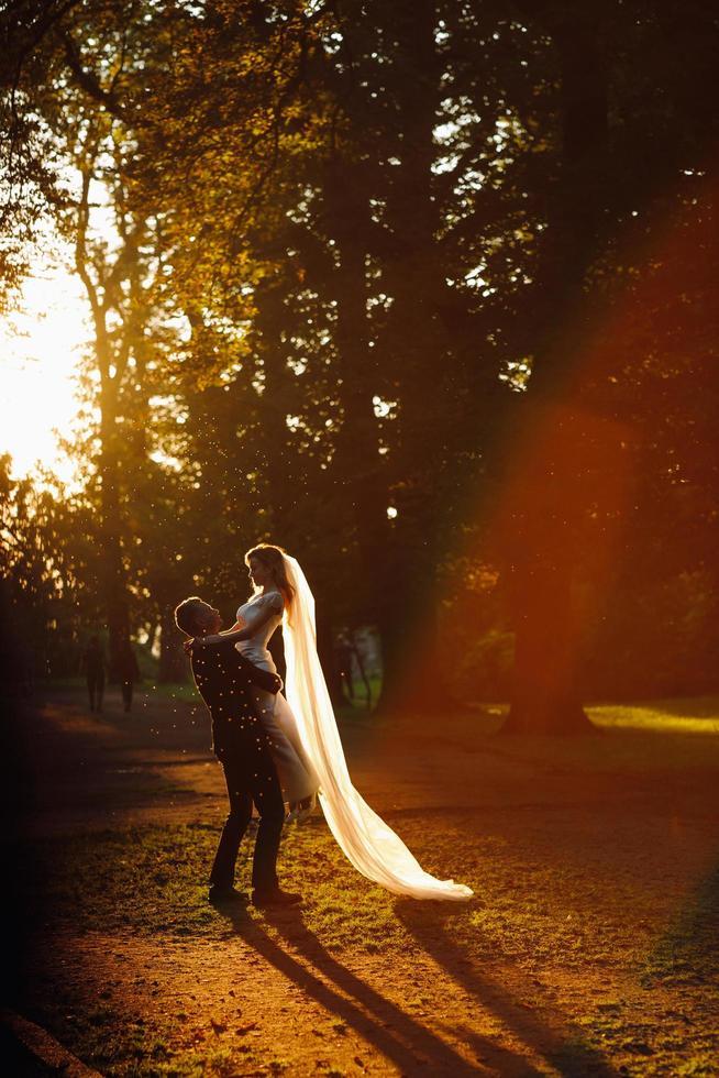 hermosa pareja de novios abrazándose en el parque con halos de sol foto