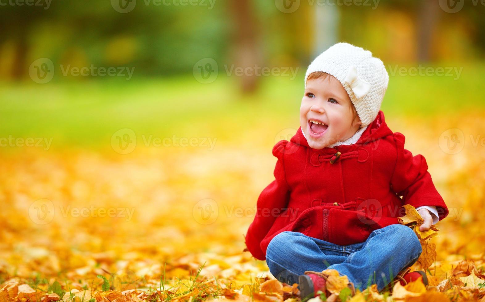 happy child on autumn nature walks in golden foliage photo
