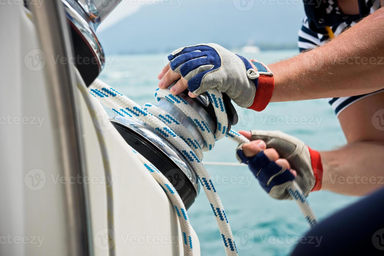 Winch and sailors hands on a sailboat photo