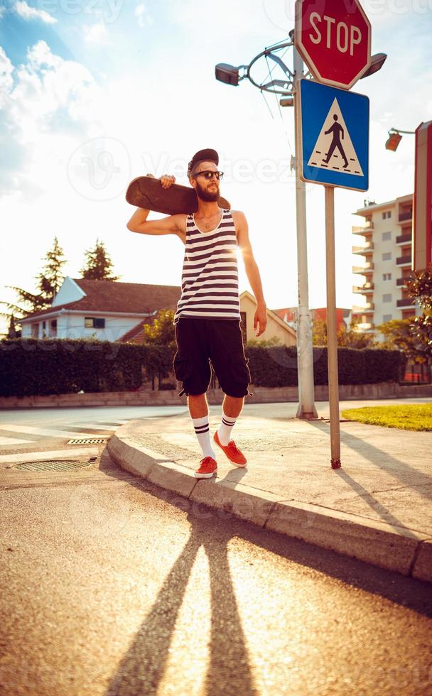 Stylish man in sunglasses with a skateboard on a street photo