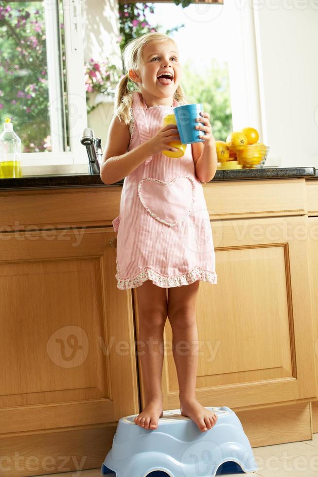 niña de pie sobre un escalón de plástico en la cocina foto